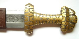 the hilt after brass inlaying and before engraving of it and silver inlaying
